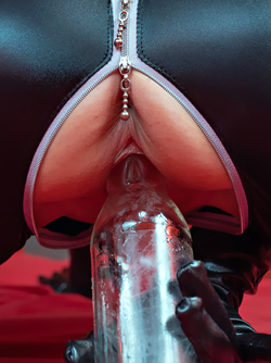 Shaved Brunette in a Fetish Catsuit Adelyn Toying with a Bottle